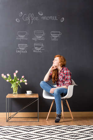 idea comfortable: Young woman sitting on a white chair beside small table, blackboard with coffee menu in the background Stock Photo
