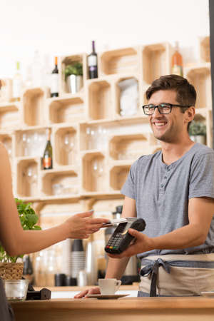 caffee: Shot of a young bartender taking an electronic payment Stock Photo