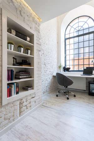 露出したレンガの壁、フロアー リングの光、シンプルなデスク、快適な椅子と明るい事務室 写真素材