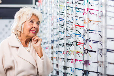 full frames: Confused senior lady standing before a rack full of different glasses frames