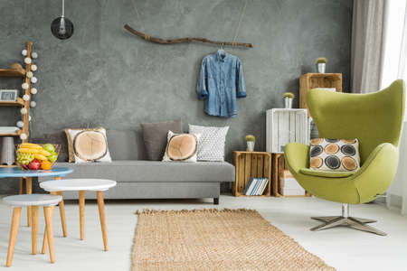 comfortable: Cozy living room in grey with sofa, comfortable armchair and creative home decorations Stock Photo