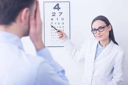 myopia: Pretty professional doctor checking the young mans vision at opticians cabinet with snellen chart