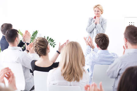 respetar: Modest young pretty woman standing surprised in the front of her work colleagues during meeting. Friendly businesspeople applauding for a woman