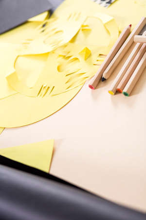 cut outs: Close-up of desk with cut outs of yellow paper and colorful pencils prepared for art classes Stock Photo