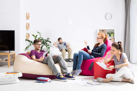 bright light: Group of students learning together in a modern apartment, sitting on colorful bean bags