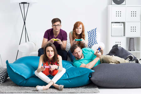 gamepads: Shot of four friends on cushion bean bags playing a video game and holding colourful gamepads in their hands