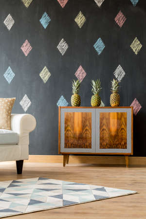 commode: Modern interior with blackboard, pattern carpet, sofa and exotic commode Stock Photo
