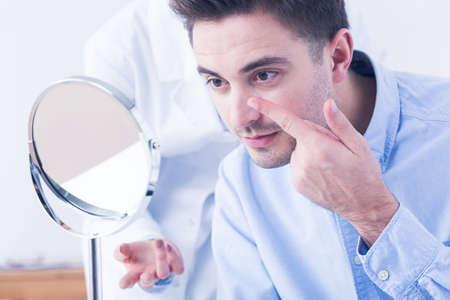 Junger stattlicher Mann mit Augenfehler versuchen, Kontaktlinsen zu tragen. Putting sie in Optiker Store auf