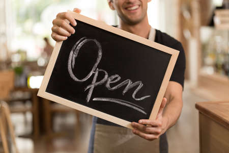 Cropped shot of a handsome cafeteria owner holding an opening sign