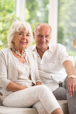 couple on couch: Portrait of happy elderly couple sitting on couch Stock Photo