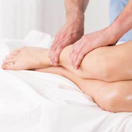 lymphatic drainage: Physical therapist doing lymphatic drainage for the legs Stock Photo