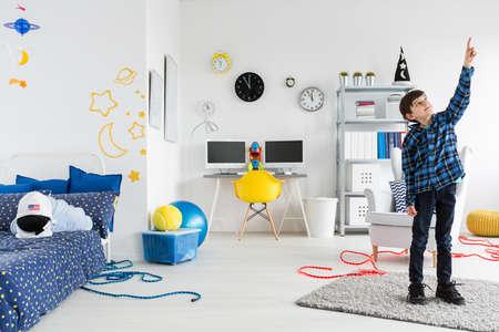 cosmos: Junge steht in seinem Zimmer und zeigt etwas auf