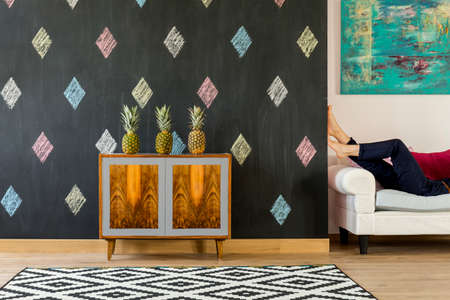 commode: Modern interior with blackboard, exotic commode, pattern carpet and sofa