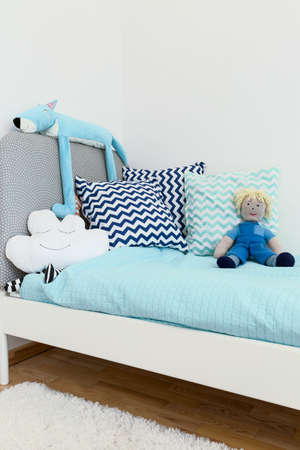 modern doll: Shot of a bed in a cosy blue childrens room Stock Photo