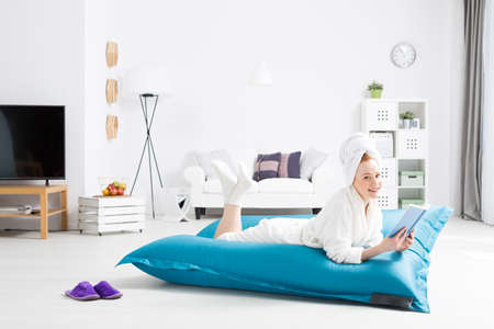 bean bag: Young woman in a nightgown lying on a blue pillow bean bag and reading a book