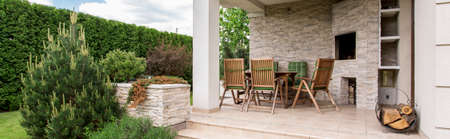 outdoor fireplace: Beautiful patio with outdoor furniture set and green plants