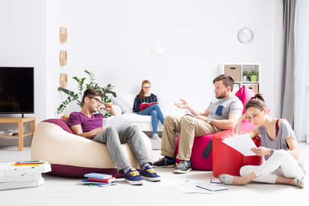 Group of students learning and talking among notes scattered around a bright room with colourful sit sacks Stock Photo