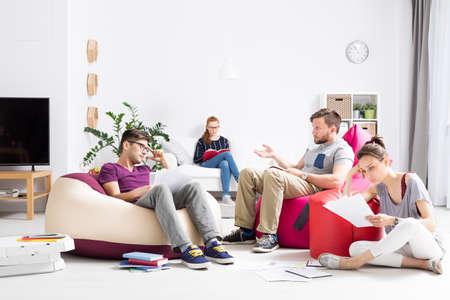 piso: Grupo de estudiantes que están aprendiendo y hablando entre notas esparcidas por una habitación iluminada con colores sacos sit