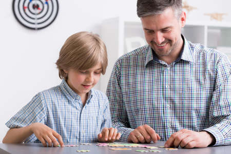 family time: Image of father and son sitting beside desk doing puzzles