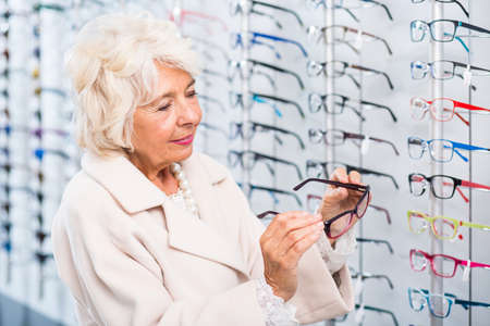 try on: Elegantly-dressed old lady holding glasses frames to try on at the opticians Stock Photo