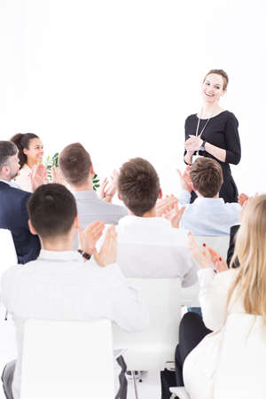 respecting: Friendly corporation businesspeople during business meeting with their young pretty boss Stock Photo