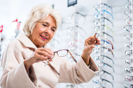 make a choice: Elderly lady holding two pairs of glasses trying to make a choice at the opticians Stock Photo