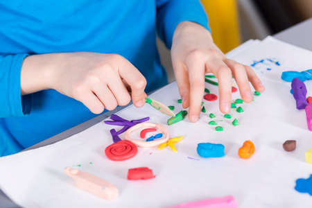 sculpt: Close-up of little creative boy doing a picture on a paper with a colorful plasticine Stock Photo
