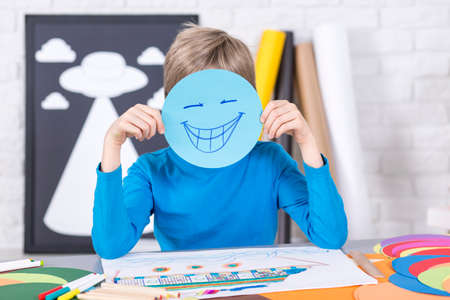 funny boy: Young funny boy holding piece of papers with smile on his face. Sitting in a studio full of colorful papers Stock Photo