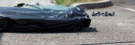 corpse: Corpse in plastic bag after car accident, horizontal