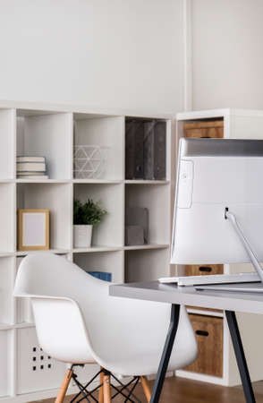 designer chair: Modern home office arranged in white, with designer chair in front of a computer desk Stock Photo