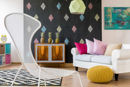 cozy: Colorful interior in new style with blackboard, exotic commode, sofa, pouffe and white chair