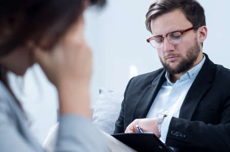 psychoanalysis: Photo of male psychologist in suit with patient during session Stock Photo