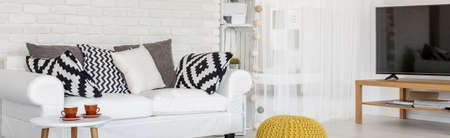 pouf: Living room with white brick wall. In room are placed couch, TV set, pouf and coffee table Stock Photo