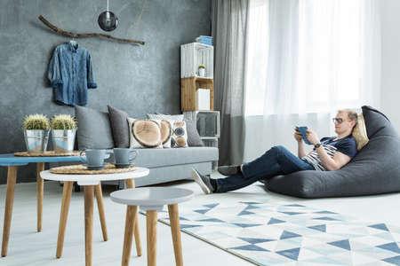 Modern style interior in grey with sofa, stylish futniture, man sitting on a bean bag Stock Photo