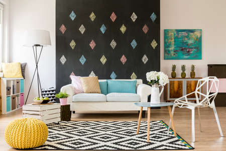 Modern flat with blackboard, pattern carpet, new crystal chair, yellow pouffe and sofa Фото со стока - 60204024