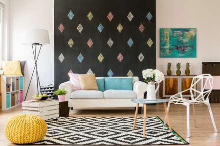 Moderne flat met bord, patroon tapijt, nieuwe kristallen stoel, geel poef en een bank Stockfoto