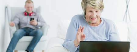 man with laptop: Shot of an older woman sitting and chatting online by the laptop with the man sitting with earphones and mobile phone on an armchair behind