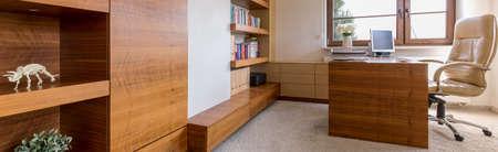 muebles de madera: oficina en casa amplia con muebles de madera maciza y silla de cuero