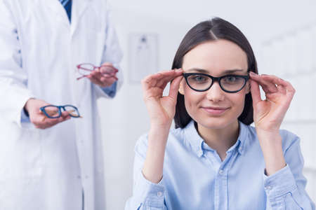 medical decisions: Smiling petty young woman choosing perfect glasses. In the background standing young optician with new pairs of glass frames
