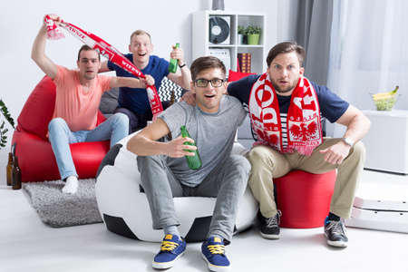 Excited group of young men sitting on bean bags, drinking beer and supporting their football team Stock Photo