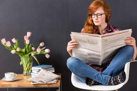 periodicos: Mujer sentada en una silla junto a una pequeña mesa, leyendo un periódico, en el fondo de la pizarra Foto de archivo
