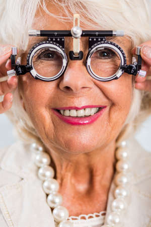 Close-up of an elderly woman having her eyes examined with a phoropter