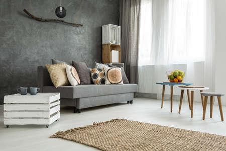 Nieuwe stijl woonkamer in grijs met een bank, doe-het-meubelen, kleine tafel en twee stoelen Stockfoto