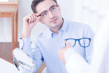 color consultation: Handsome young man trying two pair of glasses, brown and stylish and blue and modern Stock Photo