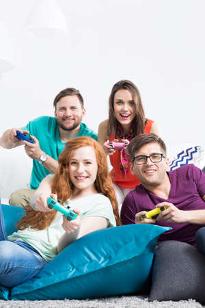 Group of friends with colorful gamepads smiling at the camera while lying on large bean bags