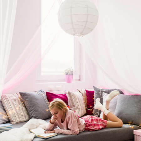 Little girl reading book on the bed