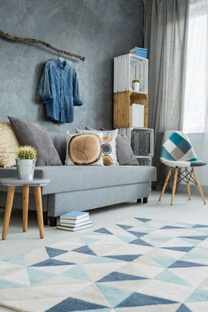 Stylish living room in grey with DIY furniture, sofa and pattern carpet