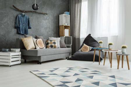 Új lakás belső szürke kanapé, modern puff, kis asztal, két szék és mintás szőnyeg