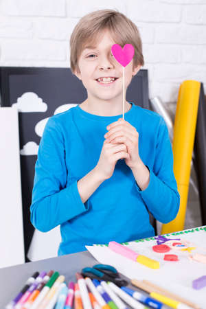 small paper: Happy young boy during art classes holding small paper heart on a stick Stock Photo