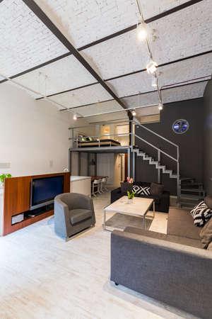 Moderno appartamento con mobili elegante soggiorno set, televisione, scale, mezzanino e il tetto di mattoni